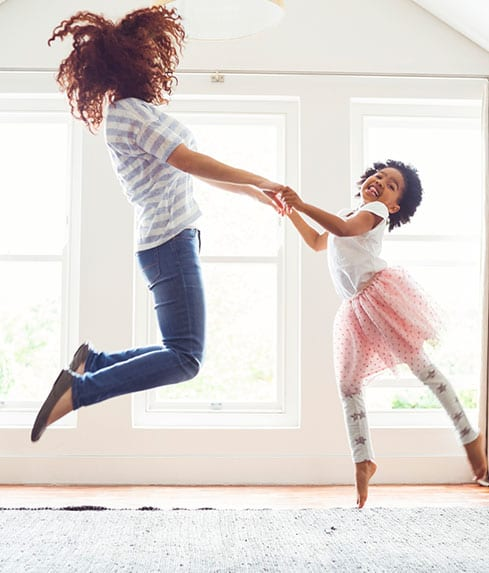 mom and daughter jumping in the air in the living room working family home