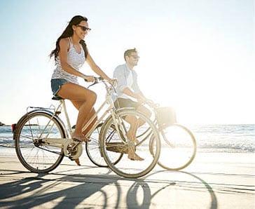 a couple riding bikes on the beach biking communities