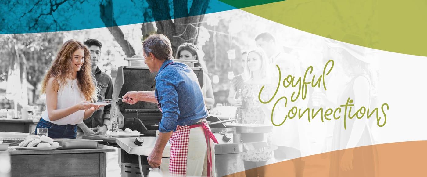 man serving hamburger to woman at bbq joyful connections