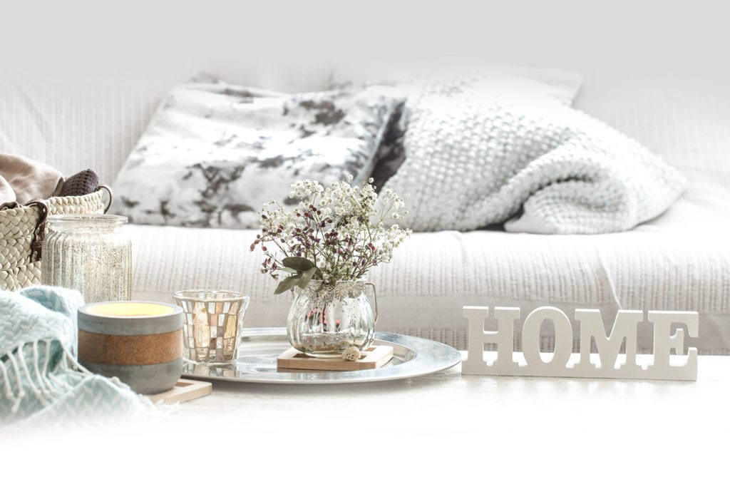 coffee table with flowers and home sign