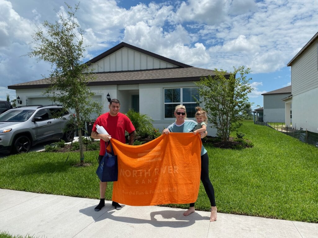 Family outside house at North River Ranch with a welcome gift