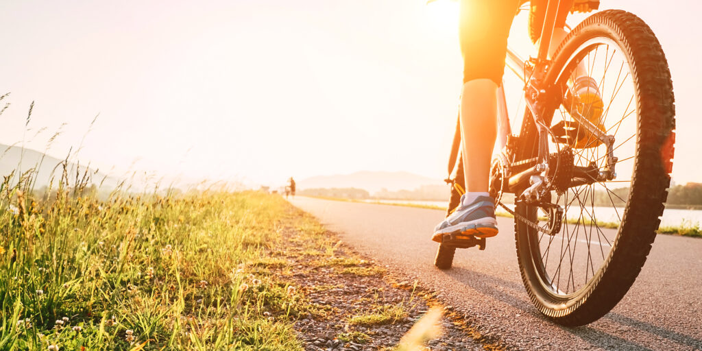 Woman feet on bicycle pedal in sunset light - New Home Community - New Construction Homes For Sale in Parrish, FL