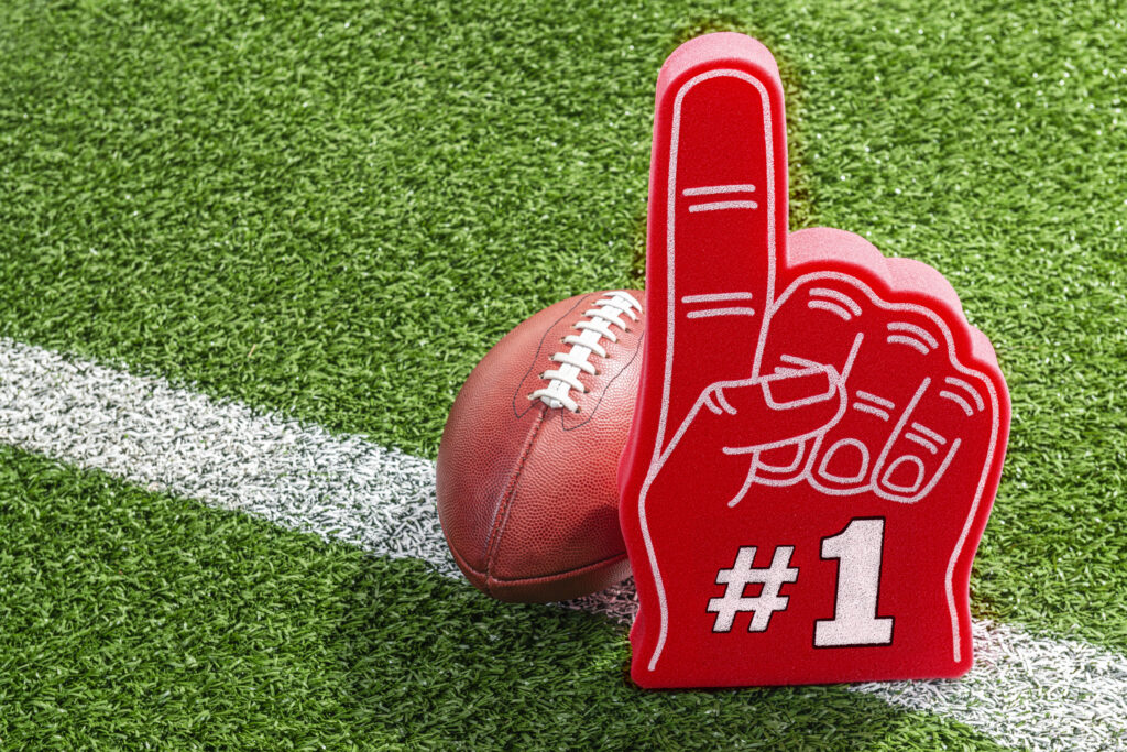 A red foam hand with a white #1 outlined in black sitting next to a leather American football that are both sitting on a white yard line on the stadium grass