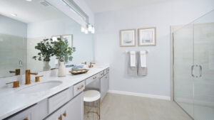 White dual vanities gold accents model home bathroom