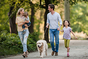 Family of four walking outdoors with their dog.