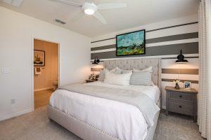 Grey striped walls master bedroom white linens tufted headboard