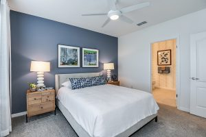 master bedroom with blue wall, white linens grey carpet
