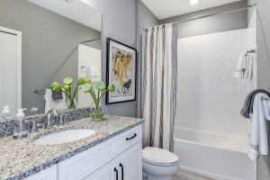 White tiled bathroom with grey and white granite