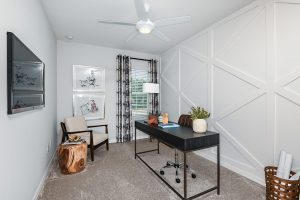 White paneled wall den with desk chair and wall tv