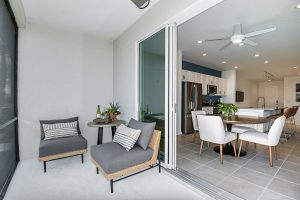 Covered lanai with grey rattan chairs and sliding door access to dining room