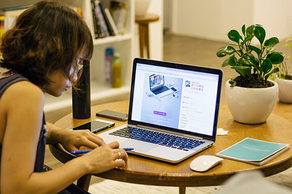 Young woman is working on her laptop  - New Home Community - New Construction Homes For Sale